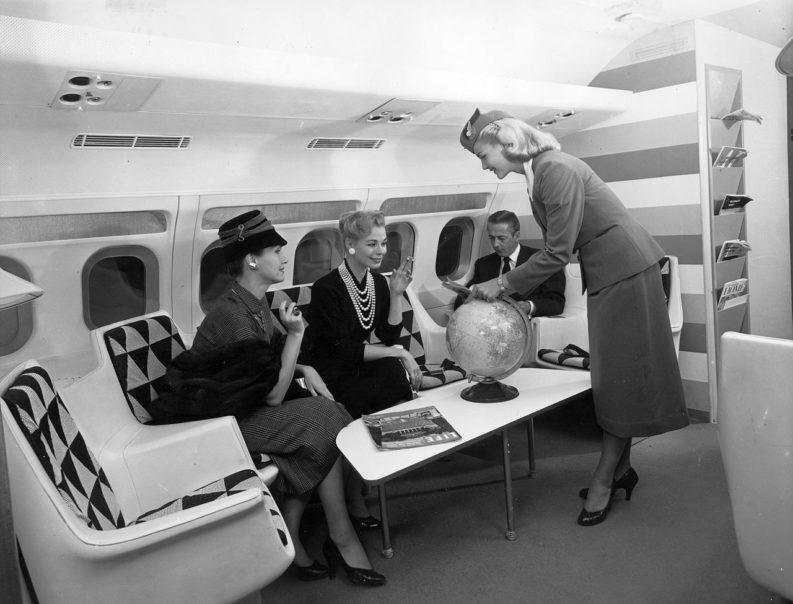jet set: hostess serve alcuni passeggeri ben vestiti nella lounge di prima classe di un Convair 880 della TWA.