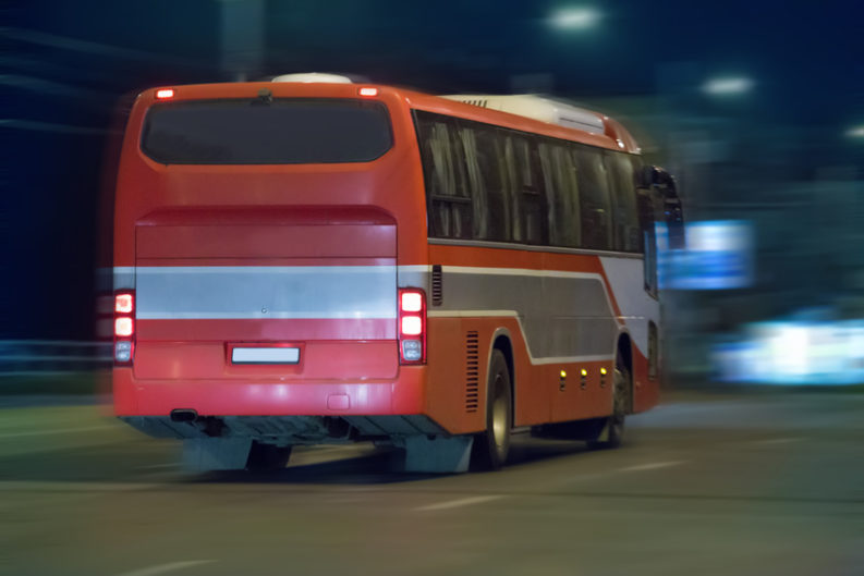 bus moves on city street at night