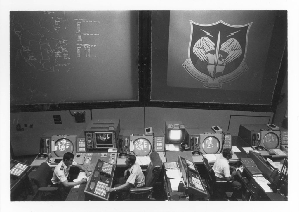 """Command post for all NORAD [North American Aerospace Defense Command] operations, including the Command's surveillance and warning sensors around the globe."" Caption from U.S. Information Agency photo. This and the next two photos were taken about 1982 so the depiction of NORAD facilities may not correspond exactly to arrangements during 1979-1980. Source: National Archives, Still Pictures Branch, RG 306-PSE, box 79"
